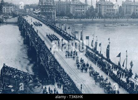 """Coronation of King George V and Queen Mary, London, 1911. 'Second day, crossing the Westminster Bridge after visiting south London'. Crowds line the bridge, with flags and a grandstand (bottom left, by the statue of Boudicca), specially erected for the occasion. At top right is St Thomas' Hospital. The coronation of King George V of the United Kingdom (1865-1936) and Queen Mary of Teck (1867-1953) took place at Westminster Abbey in London on 22 June 1911. From """"The Sphere"""", coronation edition, [June 1911] - Stock Photo"""