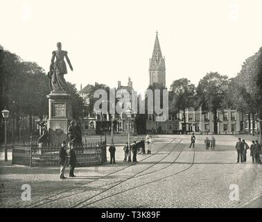 """View of the Vyverberg Square, The Hague, Netherlands, 1895. Statue, clock tower and tramlines - the city was severely damaged by bombing during the Second World War. From """"Round the World in Pictures and Photographs: From London Bridge to Charing Cross via Yokohama and Chicago"""". [George Newnes Ltd, London, 1895] - Stock Photo"""