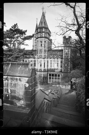 Saltwell Towers, Saltwell Park, Gateshead, Tyne & Wear, c1955-c1980. An exterior view of Saltwell Towers, showing the east side of the south elevation from an embattled turret in the garden, south-east of the house. The house was built for William Wailes, a stained glass manufacturer, in 1871 with dark brick and yellow brick dressings. The south front has two storeys with square corner turrets and a tall three storey polygonal turret on the right. Each floor of the turret has three single windows, one on each side. The main front has a continuous parapet with sloping stone capping and four - Stock Photo