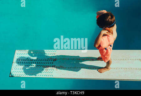 High angle shot of boy with sleeves floats on diving board preparing for dive in the pool. Boy standing on spring board at the swimming pool. - Stock Photo