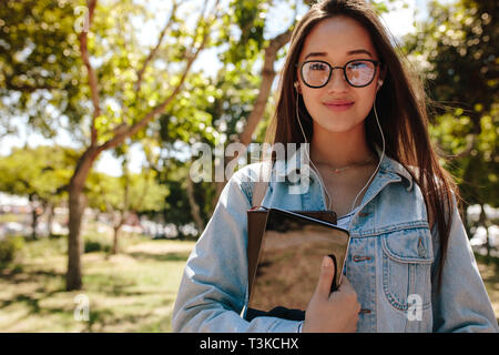 Close up of a smiling asian girl in eyeglasses standing outdoors. College student standing in campus holding a tablet pc and books. - Stock Photo