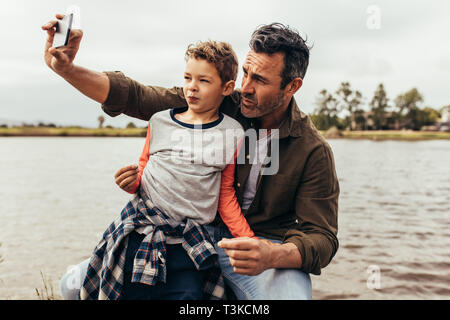 Close up of father and son taking a selfie sitting near a lake. Happy kid sitting in the lap of his father looking at the mobile phone while his fathe