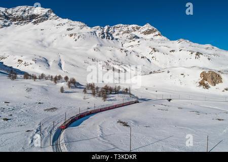 Red train of Bernina in winter season, aerial view. Bernina Express - UNESCO - Stock Photo