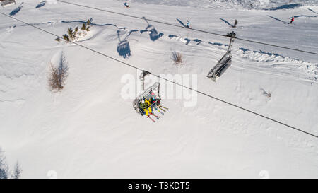 Skiers on skilift view from above. Ski resort in Europe - Stock Photo