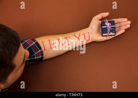 A man's hand on a brown background with letters I love you. A man in the palm of his hand holds a blue box. - Stock Photo
