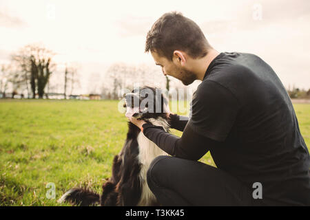 Man dog playing outdoor in the park. Young owner hugs his pet. Friendship between owner and dog. Animal love concept. - Stock Photo