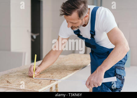 Builder measuring OSB sheet and marking it with pencil during building new house or renovation. Man in blue and white uniform working indoors - Stock Photo