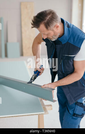 Builder cutting metal profile with scissors during interior renovation or building a new house concept - Stock Photo