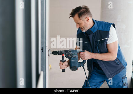 Builder cutting a round hole in wooden cladding indoors in a new build house with a power drill - Stock Photo