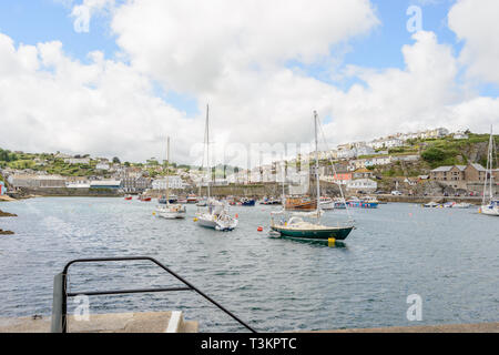 A view of boats in the harbour at Mevagissey, and buildings around it, with a blue sky and big white clouds in the background - Stock Photo