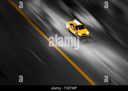 New York City yellow taxi in motion speeding down the street in Manhattan on a blurred black and white background - Stock Photo