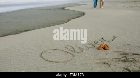 Baby name written in sand with shoes - Stock Photo