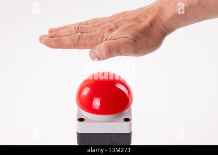 Hand pushing a red buzzer - Stock Photo