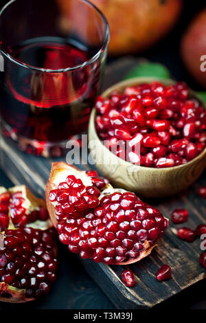 Ripe pomegranate fruit on a old black wooden vintage background. Selective focus. Stock Photo