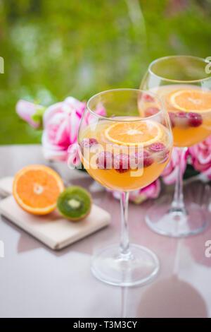 Orange vodka cocktail in elegant wine glass with kiwi, roses and raspberries - Stock Photo