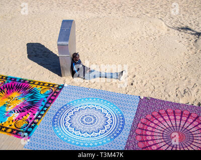 BARCELONA, SPAIN-MARCH 18, 2019: African refugee carpet vendor on the Barceloneta beach - Stock Photo