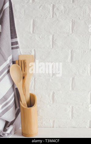 Simple rustic kitchenware: wooden or bamboo cutlery and towel in interior of white kitchen. Rustic style. Home Kitchen Decor. - Stock Photo
