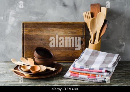 Simple rustic kitchenware: ceramic plates, wooden or bamboo cutlery, vintage cutting board and towels in interior of kitchen. Rustic style. Home Kitch - Stock Photo