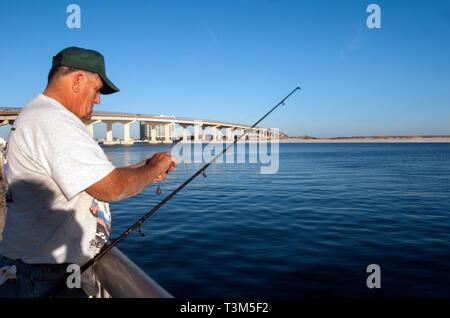 A fisherman baits his hook at Florida Point fishing pier Nov. 12, 2009 in Orange Beach, Alabama. - Stock Photo