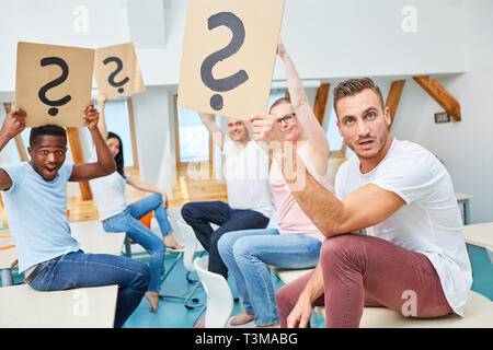 Young business start-up team holding cardboard sign with question mark up in the office - Stock Photo