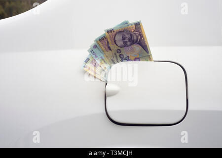 money in the car fuel tank. Romanian Leu currency concept for expensive gas - Stock Photo