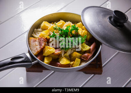 fried egg with sausage and potato in a frying pan on a white wood background - Stock Photo