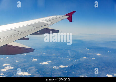 Aircraft wing on the clouds, flies on the city background. - Stock Photo