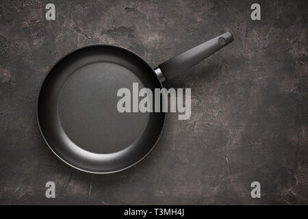 Empty Frying Pan Black on Dark Stone Surface. Culinary Background. - Stock Photo