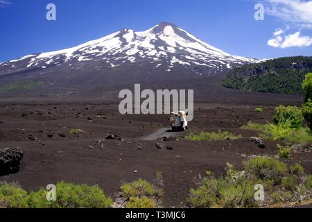 Wide field of volcanic lava ash on peak of black Volcano Llaima with spots and stripes of snow and ice contrasting with blue sky - Conguillio NP - Stock Photo