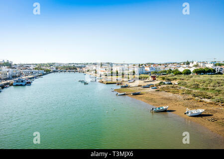 Cityscape fo Tavira with fisherman boats and roman bridge over Gilao river, Algarve, Portugal - Stock Photo