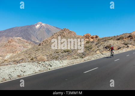 Cyclist on a road bike enjoying the descent from the Mount Teide cable car station on the TF-21, Tenerife - Stock Photo