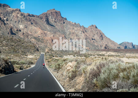 Cyclist on a road bike enjoying the descent from the Mount Teide cable car station on the TF-21 (towards the TF-38 south), Tenerife - Stock Photo