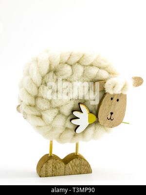 Figure of a sheep made of wool and wood on a white background - Stock Photo
