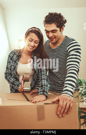 The young happy couple is moving into a new house. They are packing boxes with things to their new living room. - Stock Photo