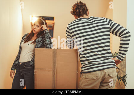 The young couple is moving into a new house. They are tired after bringing a lot ofboxes with things to their new home. - Stock Photo