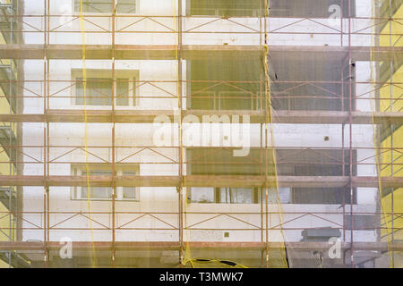 Building facade renovation, old house reconstruction, repair. Scaffold in front of building facade covered with yellow transparent fabric - Stock Photo