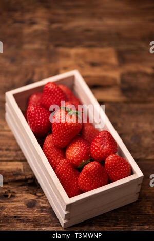 Fresh strawberry in basket on wooden table - Stock Photo