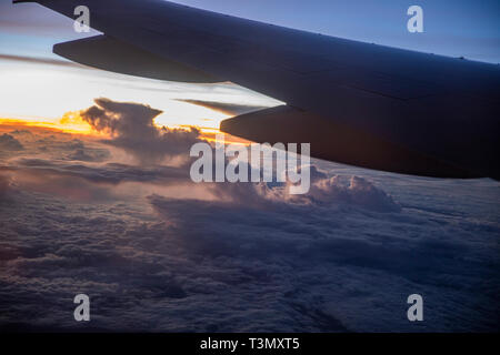View from beautiful large tinted window of Qantas Boeing 787 dreamliner flying above the clouds approaching Sydney on direct flight from LAX - Stock Photo
