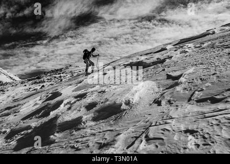 Group of mountaineers ascend and reach the top of one of the most spectacular peaks  in Retezat National Park, Romania, the Summit of Retezat on skis. - Stock Photo