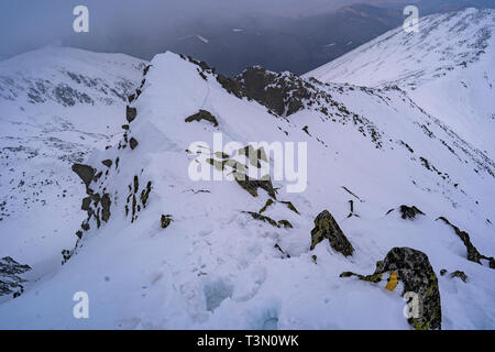 Group of mountaineers ascend and reach the top of one of the most spectacular peaks in Retezat National Park, Romania - Stock Photo