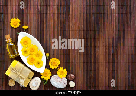 Spa composition with natural soap, aroma oil in bottles and flowers on bamboo mat. Top view - Stock Photo