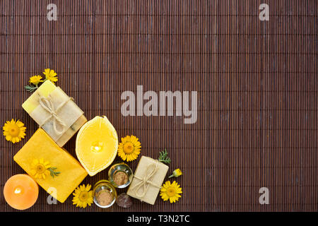 Spa composition with natural soap, candles, aroma oil in bottles and flowers on bamboo mat. Top view - Stock Photo