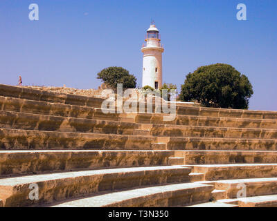 Roman odeion, restored 1970's, and lighthouse, Kato Pafos, Cyprus - Stock Photo