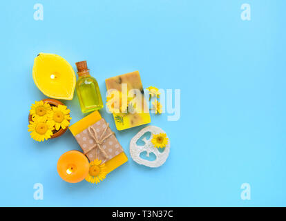 Spa composition with natural soap, candles, aroma oil in bottles and flowers on blue background. Top view - Stock Photo