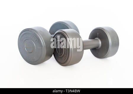 Two grey plastic-covered 3kg dumb-bell weights isolated on a white background - Stock Photo