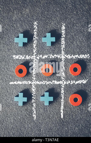 Top view of tic tac toe game (noughts and crosses) on dark background. - Stock Photo