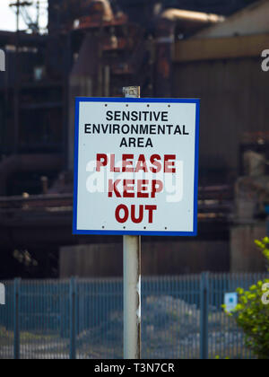 A warning sign for a Sensitive Environmental Area Please Keep Out   erected outside the now disused steel making blast furnace plant in Redcar  North  - Stock Photo