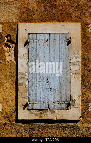 Weathered old blue shutters in an ochre wall closed against the afternoon sun in Rousillion, Provence, France. - Stock Photo