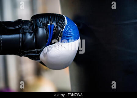 Boxing concept. Hand of boxer in glove hits black sandbag c - Stock Photo