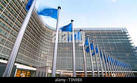 European Union EU flags waving in front of the Berlaymont building, headquarters of the European Commission in Brussels. - Stock Photo